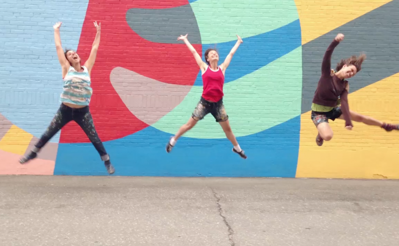A still from the documentary short Oak Street Mural where three people are jumping in front of the mural.