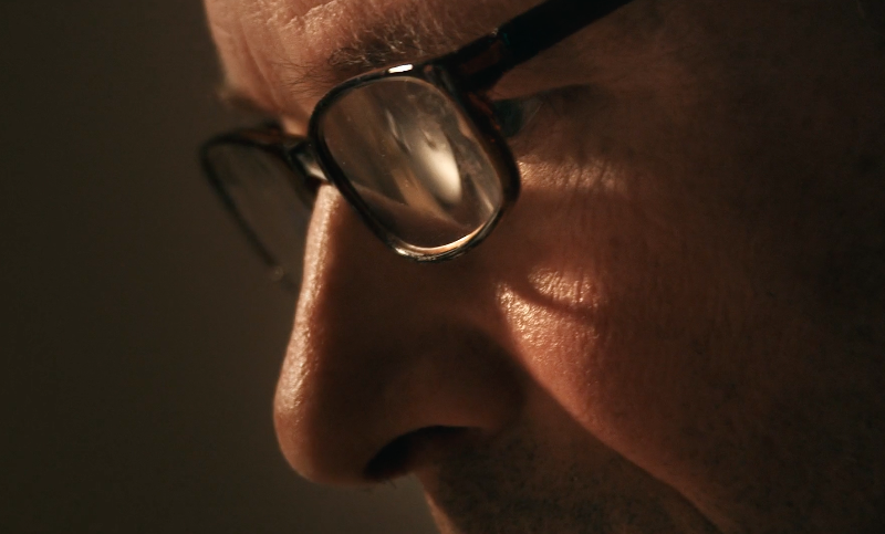 A closeup of Steven Valleau working with glasses on from Madeleine Cohen's documentary Bird Carver.