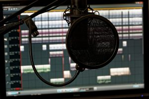 Microphone with pop filter in front of computer screen with audio software.