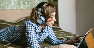 Woman with headphones laying on bed watching video on tablet.