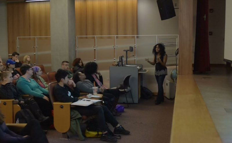 Raeshelle Cooke speaking to students about film in an auditorium.